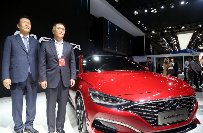 Hyundai Motor Group Vice Chairman Chung Eui-sun (R) poses next to the Lafesta sports sedan in Beijing on April 25, 2018. (Yonhap)