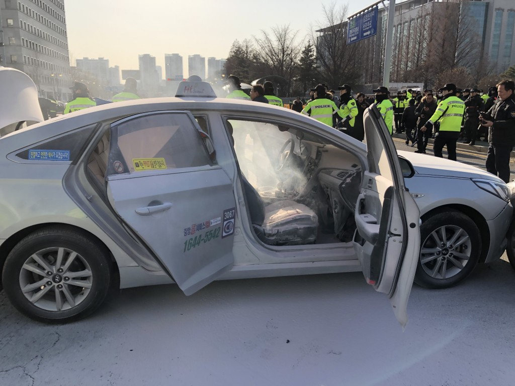 The photo, taken Feb. 11, 2019, shows a taxi after a fire set by the driver was put out by firefighters near the National Assembly in western Seoul. (Image: Yonhap)