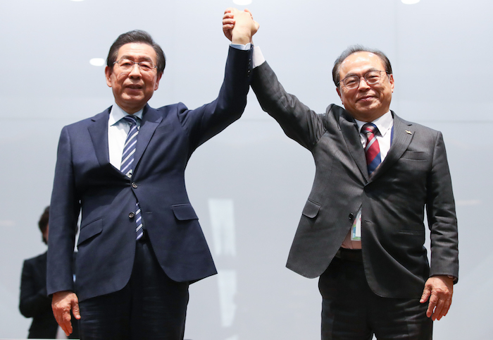Seoul Mayor Park Won-soon (L) and Busan Mayor Oh Keo-don raise their arms at the Jincheon National Training Center in Jincheon, 90 kilometers south of Seoul, on Feb. 11, 2019, after Seoul defeated Busan to become the South Korean candidate city for a joint bid to host the 2032 Summer Olympics with North Korea. (Image: Yonhap)