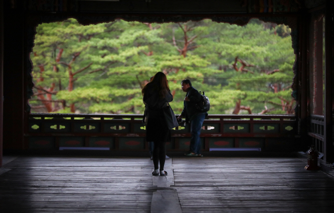 Tourists enjoying the view on the second floor of Gyeonghoeru Pavilion at Gyeongbok Palace in Seoul. (Yonhap)