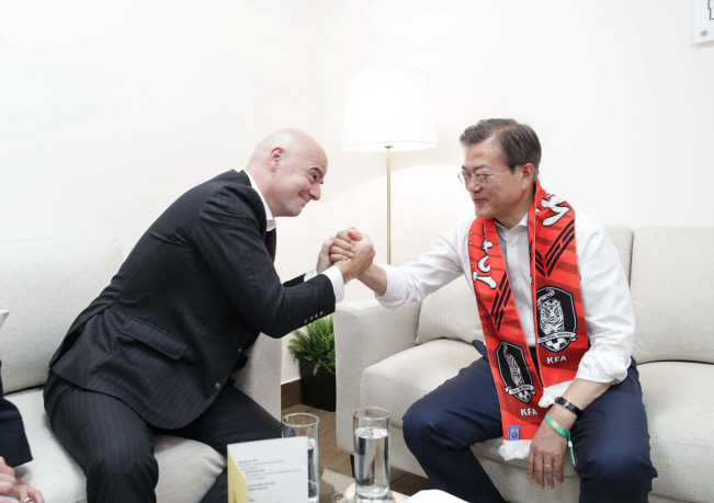 FIFA President Gianni Infantino (L) clasps hands with South Korean President Moon Jae-in at Rostov Arena in Rostov-on-Don, Russia, on June 23, 2018 after attending a Group F match between South Korea and Mexico at the 2018 FIFA World Cup. (Yonhap)