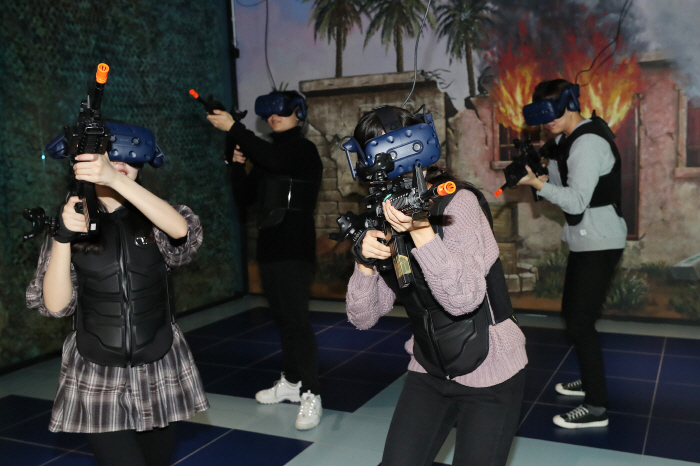 Players enjoy a virtual reality shooting game at VR Station in Gangnam, Seoul, on Dec. 4, 2018. (Yonhap)