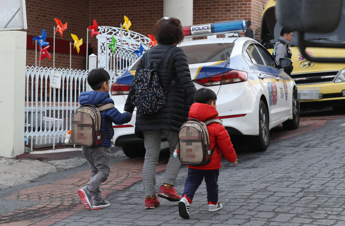 A mother takes her children to a private preschool in Daegu, 300 kilometers southeast of Seoul, on March 4, 2019, for a care service offered in lieu of regular classes due to a collective protest against a government reform drive on private kindergartens. (Yonhap)