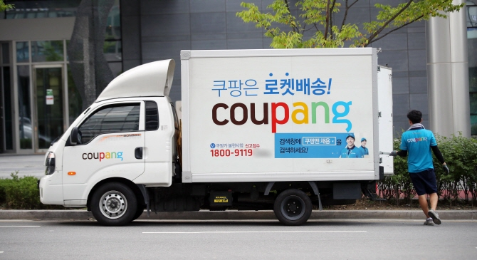 A delivery man for Coupang Inc., South Korea's leading e-commerce operator, loads a parcel delivery truck in Seoul on Aug. 8, 2018. (Yonhap)