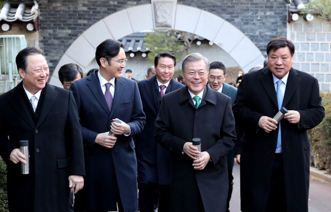 President Moon Jae-in (2nd from R) takes a walk in a garden at Cheong Wa Dae with South Korean business leaders on Jan. 15, 2019. Samsung Vice Chairman Lee Jae-yong (2nd from L) and SK Chairman Chey Tae-won (C, back row) were among the businesspeople. (Yonhap)