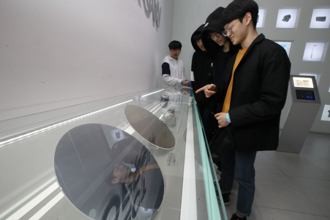 Visitors to Samsung Electronics Co.'s d'light, a global promotion and exhibition center inside its Seoul headquarters, look at a wafer, a thin slice of a semiconductor, on April 1, 2019. (Yonhap)
