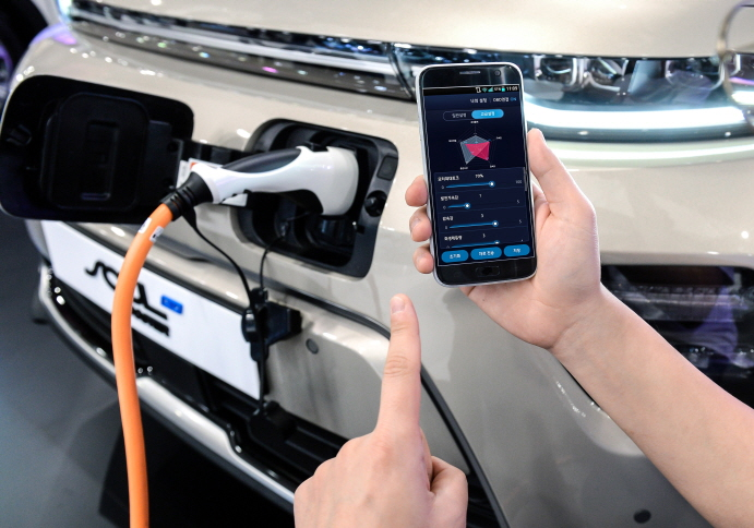 An engineer testing smartphone-based EV tune-up technology on Kia Motors' Soul EV model. (image: Hyundai Motor Group)