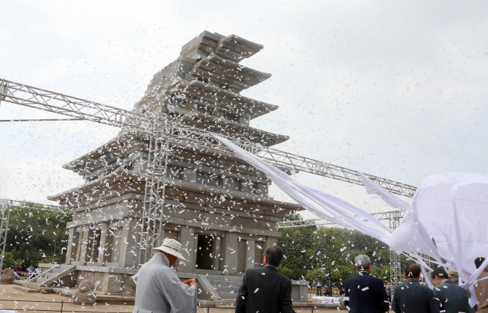 Participants in a ceremony marking the completion of 20-year-long restoration of the stone pagoda at Mireuk Temple remove a white cloth covering the pagoda in the southwestern provincial city of Iksan on April 20, 2019. (Yonhap)