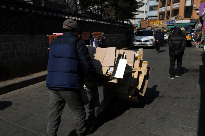 An old man pushing a trolley loaded with cardboard for recycling, a common scene in South Korea, where a rising number of elderly people live in poverty. (Yonhap)