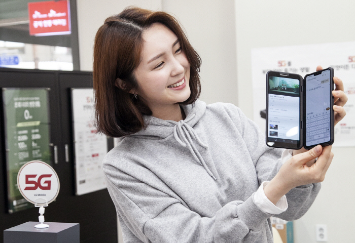 A model shows an LG V50 ThinQ with a second screen that goes on sale in South Korea on May 10, 2019. (image: SK Telecom Co.)