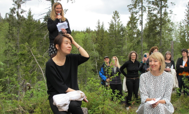 "South Korean novelist Han Kang (L) hands over her script to Katie Paterson as part of the Norwegian arts project ""Future Library"" at a forest in Oslo, Norway, on May 26, 2019. (Yonhap)"