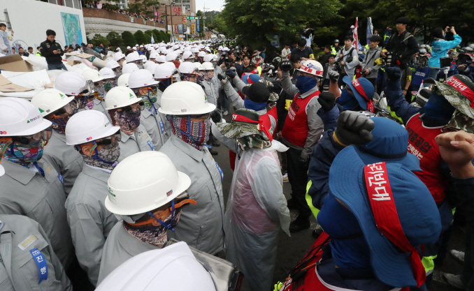 Unionized Hyundai Heavy Industries Co. workers confront the company's other workers in front of a building in the southeastern city of Ulsan on May 31, 2019, as they stage a sit-in protest to impede the shipbuilder's shareholders' meeting the same day for the implementation of a split-up plan by the company for a merger with Daewoo Shipbuilding and Marine Engineering Co. (Yonhap)