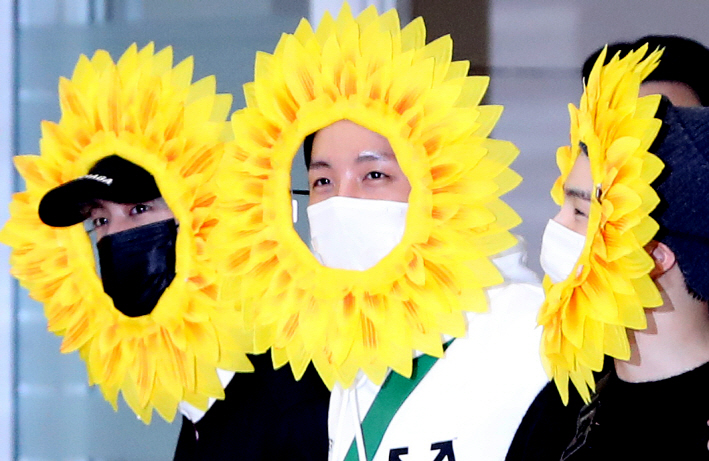 BTS' Jin (L), J-Hope (C) and Suga (R), wearing sunflower accessories, arrive at Incheon International Airport, west of Seoul, on June 10, 2019. (Yonhap)