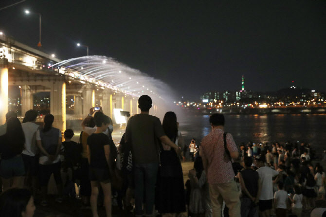 Citizens take a break from a tropical night at a Han River park in Seoul (Yonhap)