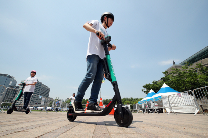 Currently, electric kickboards are legally categorized as cars, which prevents them from being used on pedestrian or bicycle paths. (Yonhap)