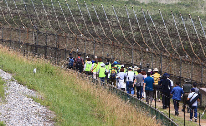Tourists walk along a trail adjacent to the Demilitarized Zone (DMZ), named the DMZ Peace Trail, in the northeastern border county of Goseong on June 26, 2019, nearly two months after its opening. (Yonhap)
