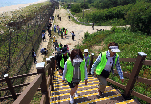 Tourists walk along a trail adjacent to the Demilitarized Zone (DMZ), named the DMZ Peace Trail, in the northeastern border county of Goseong June 26, 2019, nearly two months after its opening. (Yonhap)