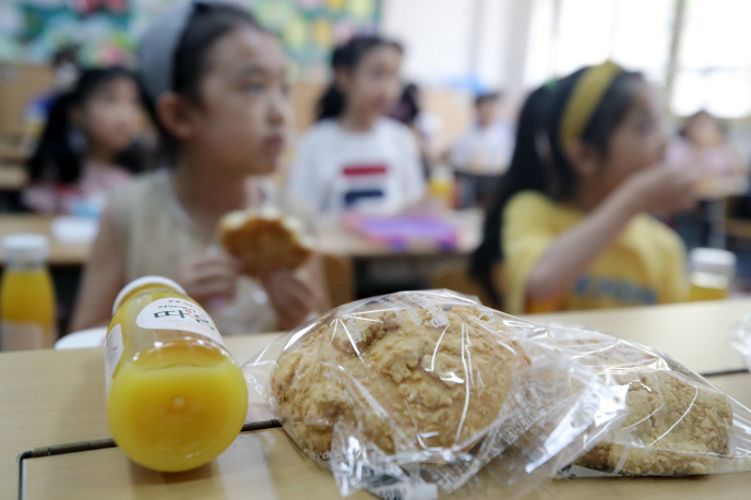 Bread and beverages are distributed to students at an elementary school in Busan, 450 kilometers southeast of Seoul, at lunchtime on July 3, 2019. (Yonhap)