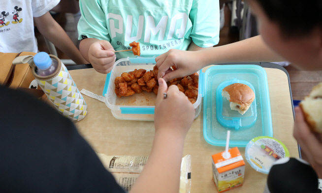 Pupils at an elementary school in Busan share a lunch box and substitute food as their cafeteria suspended its meal service due to a strike by contract workers on July 4, 2019. (Yonhap)
