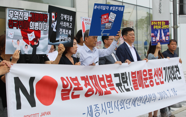 Civic activists hold a protest as part of a boycott campaign against Japanese goods while showing a list of Japanese brands in front of a branch of Uniqlo, a Japanese casual wear retailer, in Sejong on July 18, 2019. (Yonhap)