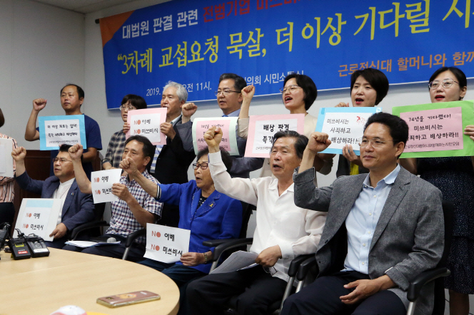 Members of a civic group raise their fists during a press conference in the southwestern city of Gwangju on July 23, 2019. (Yonhap)