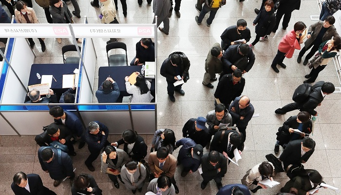Middle-aged job seekers wait for interviews at a joint fair in Busan. (Yonhap)
