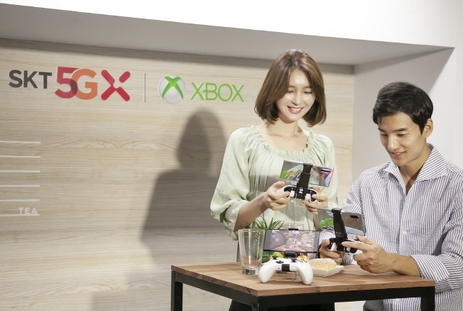 Models pose with smartphones installed with the Project xCloud platform. (image: SK Telecom Co.)