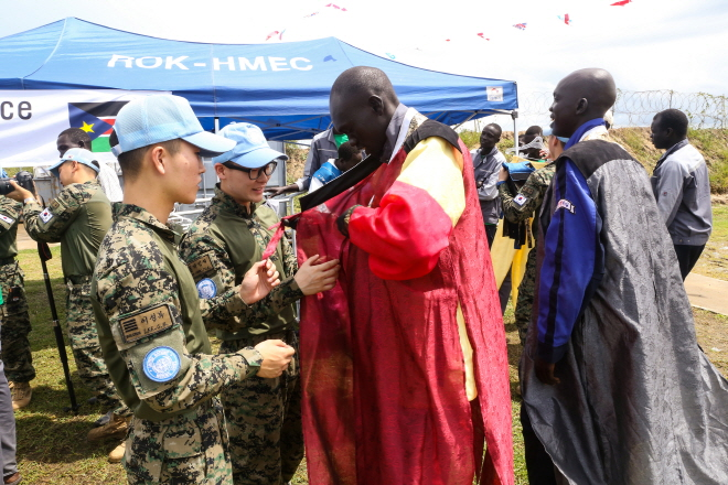South Korean soldiers from the Hanbit Unit help local residents in South Sudan try on hanbok, Korean traditional attire, on Sept. 24, 2018. (image: Joint Chiefs of Staff)