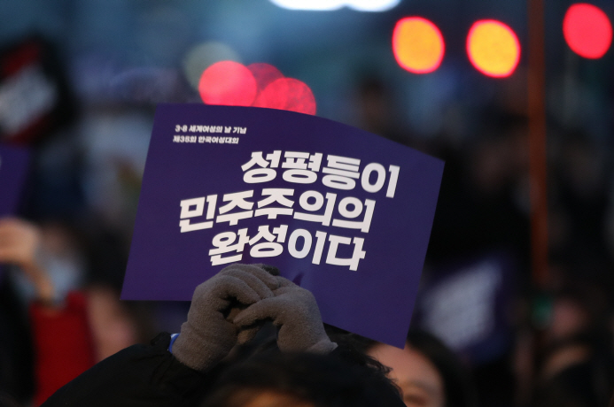 "A person attending a Women's Day ceremony on March 8, 2019, holding a sign that reads, ""Gender equality completes democracy."" (Yonhap)"