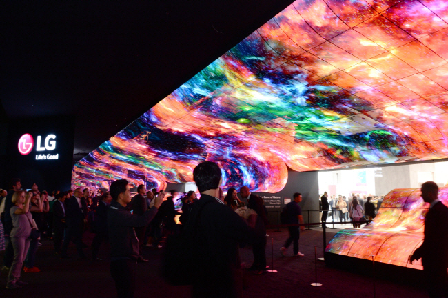 Visitors to LG Electronics Inc.'s booth at the IFA technology show in Berlin watch videos displayed on an artificial waterfall made of 260 55-inch OLED panels on Sept. 8, 2019. (image: LG Electronics)