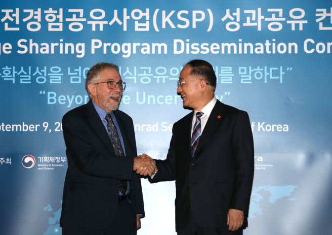 South Korean Finance Minister Hong Nam-ki (R) shakes hands with Paul Krugman, an economics professor at the City University of New York's Graduate Center, at an international conference on a knowledge sharing program at a Seoul hotel on Sept. 9, 2019. (Yonhap)