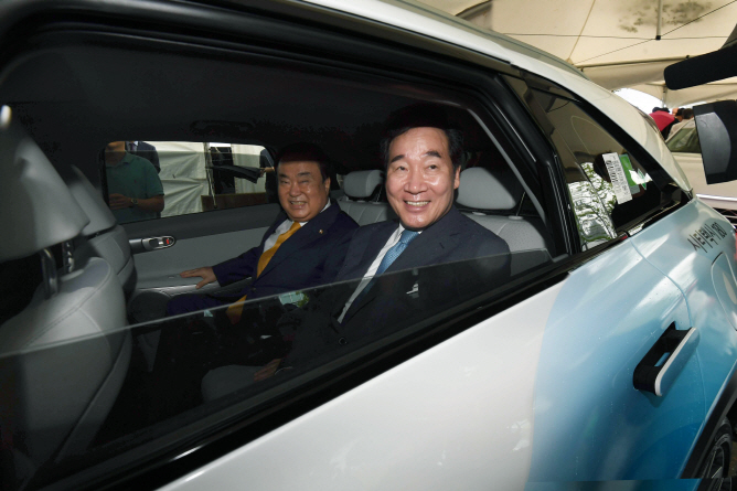 Prime Minister Lee Nak-yeon (R) and National Assembly Speaker Moon Hee-sang ride a hydrogen fuel cell taxi on Sept. 10, 2019, after attending the opening ceremony of a new hydrogen charging station at the National Assembly building in western Seoul. (Yonhap)