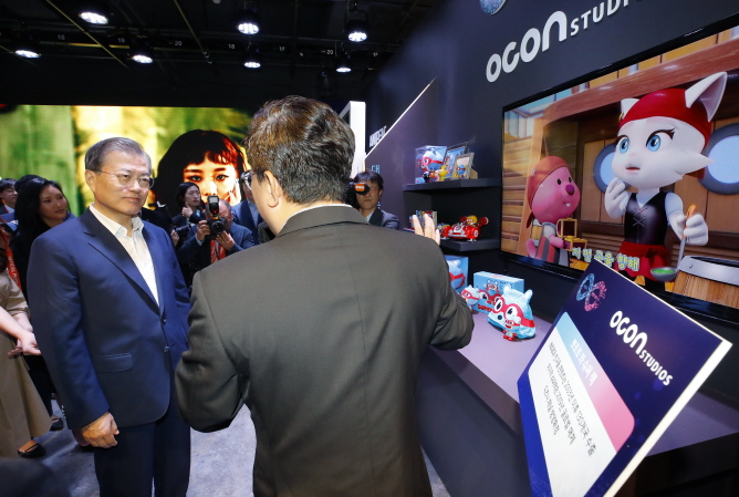 President Moon Jae-in (L) is briefed on the animated character Pororo before unveiling South Korea's three innovation strategies for the content industry at the Korea Creative Content Agency in Seoul on Sept. 17, 2019. (Yonhap)