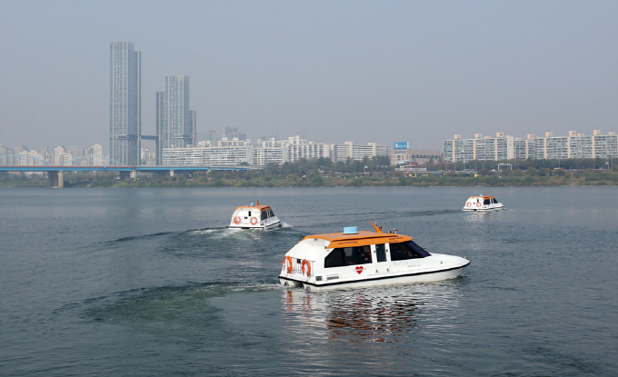 Water taxis sail on the Han River flowing through the center of Seoul. (Yonhap)