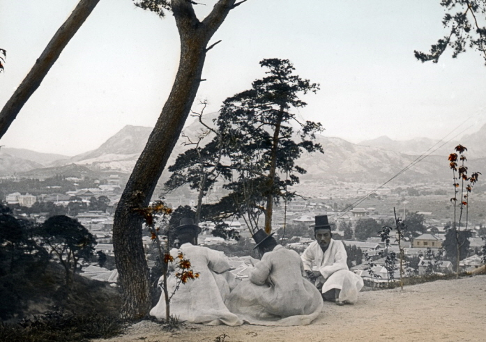Three men sitting under a pine tree on Mount Nam in Seoul. (image: Seoul Museum of History)