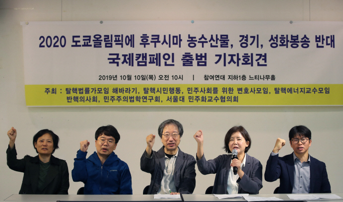 Environmental academics and activists hold their fists up at a press conference announcing the launch of their campaign on Oct. 10, 2019. (Yonhap)