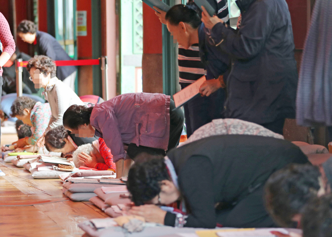 Parents praying for their children taking the national college admission exam at Jogye Temple in central Seoul on Oct. 15, 2019. (Yonhap)