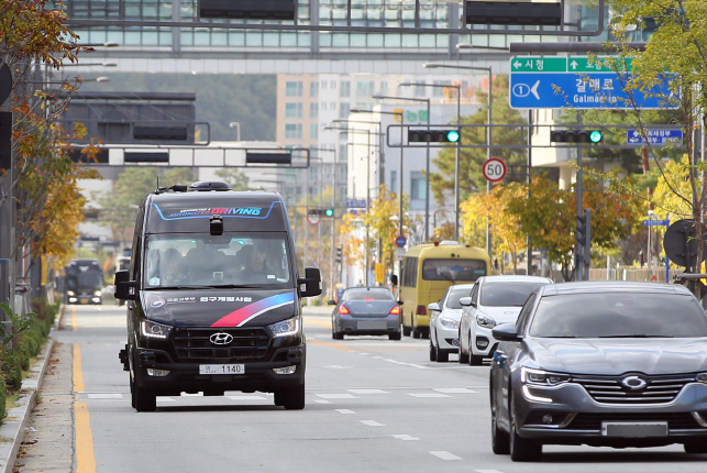 An autonomous bus (L) on a road in Sejong on Oct. 29, 2019. (Yonhap)