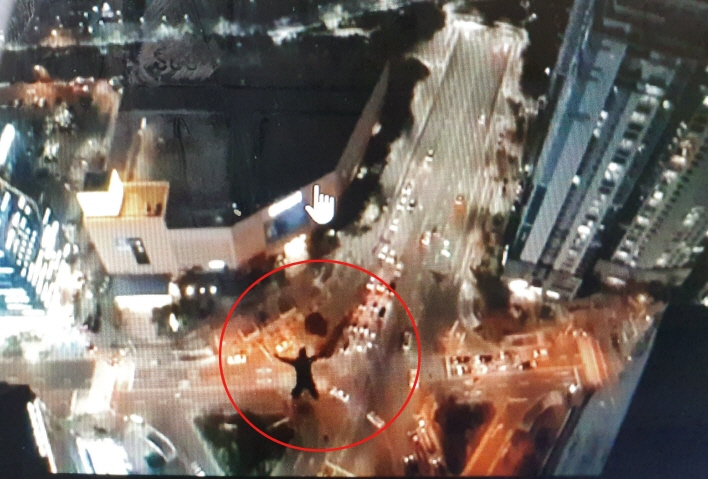 This image of a man base jumping from a skyscraper in Busan is captured from a video posted on the jumper's social media account. (Yonhap)