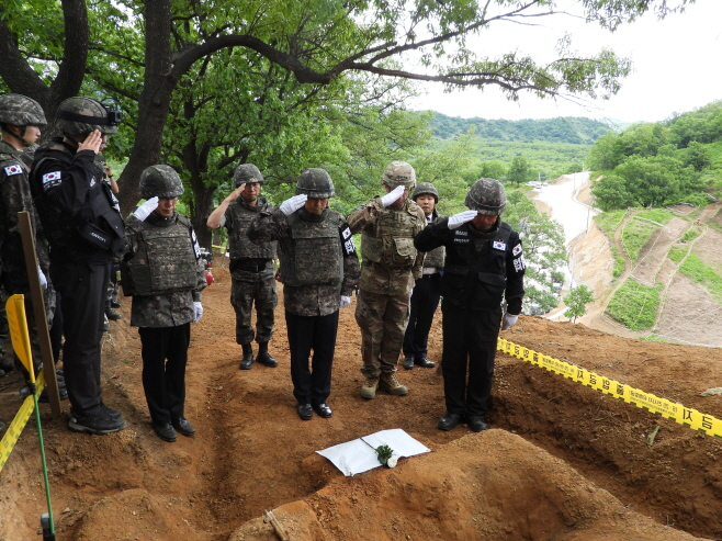 Soldiers give a salute in front of the remains of a South Korean soldier killed in the 1950-53 Korean War inside the Demilitarized Zone (DMZ). (Yonhap)