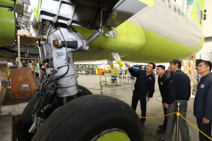Aviation officials looking at a B737-NG plane operated by low-cost carrier Jin Air as it undergoes repair work on structural cracks in western Seoul on Nov. 11. (image: Ministry of Land, Infrastructure and Transport)