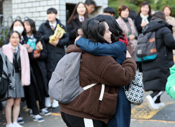 A parent hugs her daughter, who is taking this year's College Scholastic Aptitude Test at a high school in the southeastern port city of Busan on Nov. 14, 2019. (Yonhap)