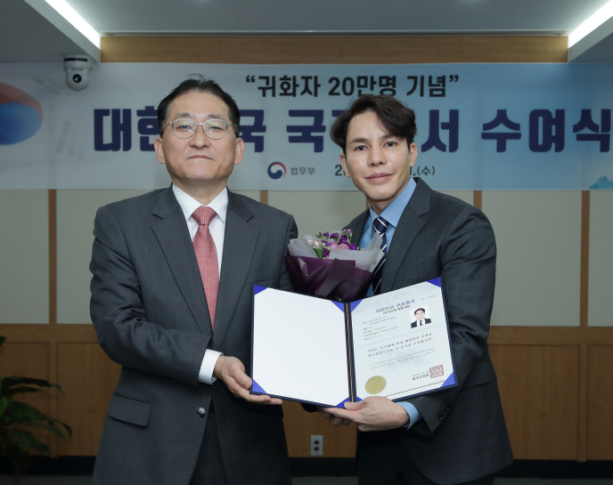 Cha Gyu-geun (L), commissioner of the Korea Immigration Service, and Prof. Krisda Chaemsaithong, hold the South Korean citizenship certificate at the government complex in Gwacheon, south of Seoul, on Nov. 20, 2019. (image: Ministry of Justice)