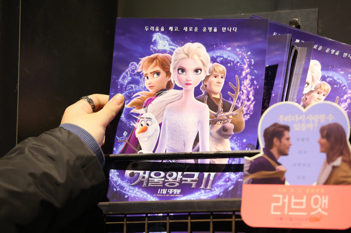 "a South Korean moviegoer holding up a promotional leaflet of ""Frozen 2"" at a local movie theater. (Yonhap)"