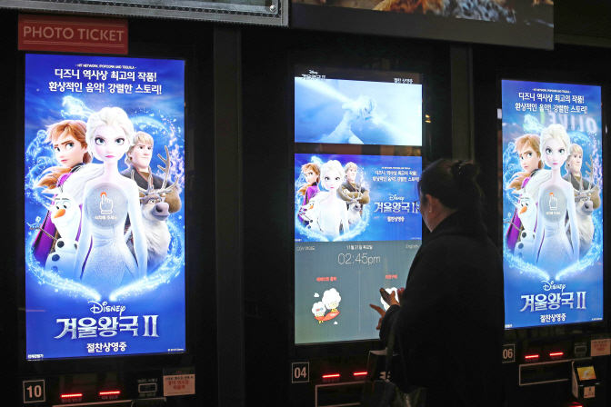 A moviegoer in the process of buying movie tickets on a machine at a local movie theater. (Yonhap)
