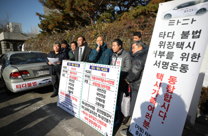 A group of taxi drivers stages a rally in front of Seoul Central District Court, calling for the suspension of the Tada service, on Dec. 2, 2019. (Yonhap)