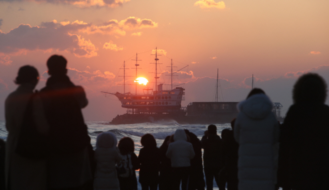 This undated file photo shows people watching the sunrise on Jeongdongjin Beach in Gangneung, Gangwon Province. (Yonhap)