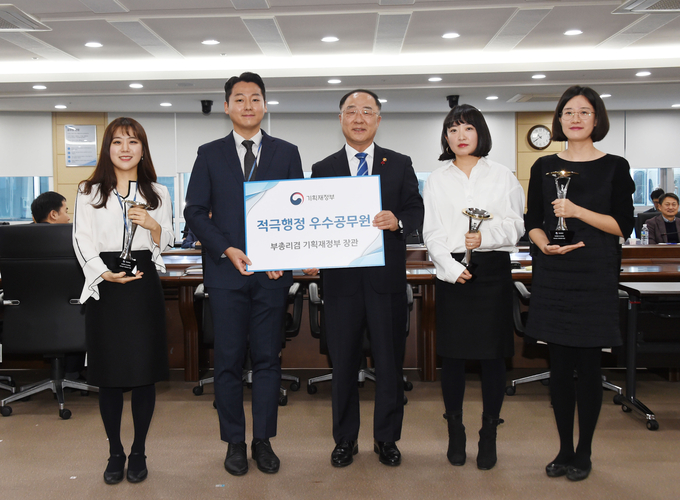 """Four officials from the Ministry of Economy and Finance, who were selected as outstanding public servants for """"Active Administration,"""" received an award Thursday from Finance Minister Hong Nam-ki (C). (image: Ministry of Economy and Finance)"""