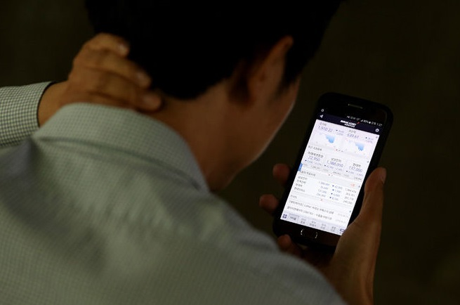 An investor monitoring share prices on a smartphone. (Yonhap)