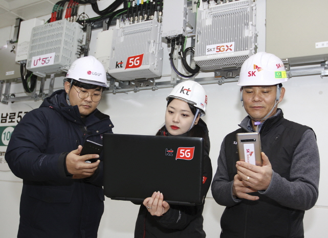 In this photo provided by South Korea's mobile carriers, engineers from LG Uplus Corp. (L), KT Corp. (C) and SK Telecom Co. check their 5G network operation at a subway station in Gwangju, some 330 kilometers south of Seoul.